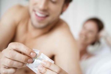 man opening a condom-best condoms to stay longer in bed