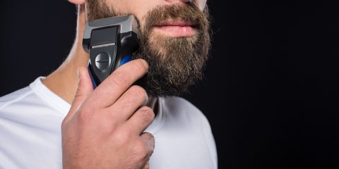 Portrait of young man is shaving his beard. Black background.